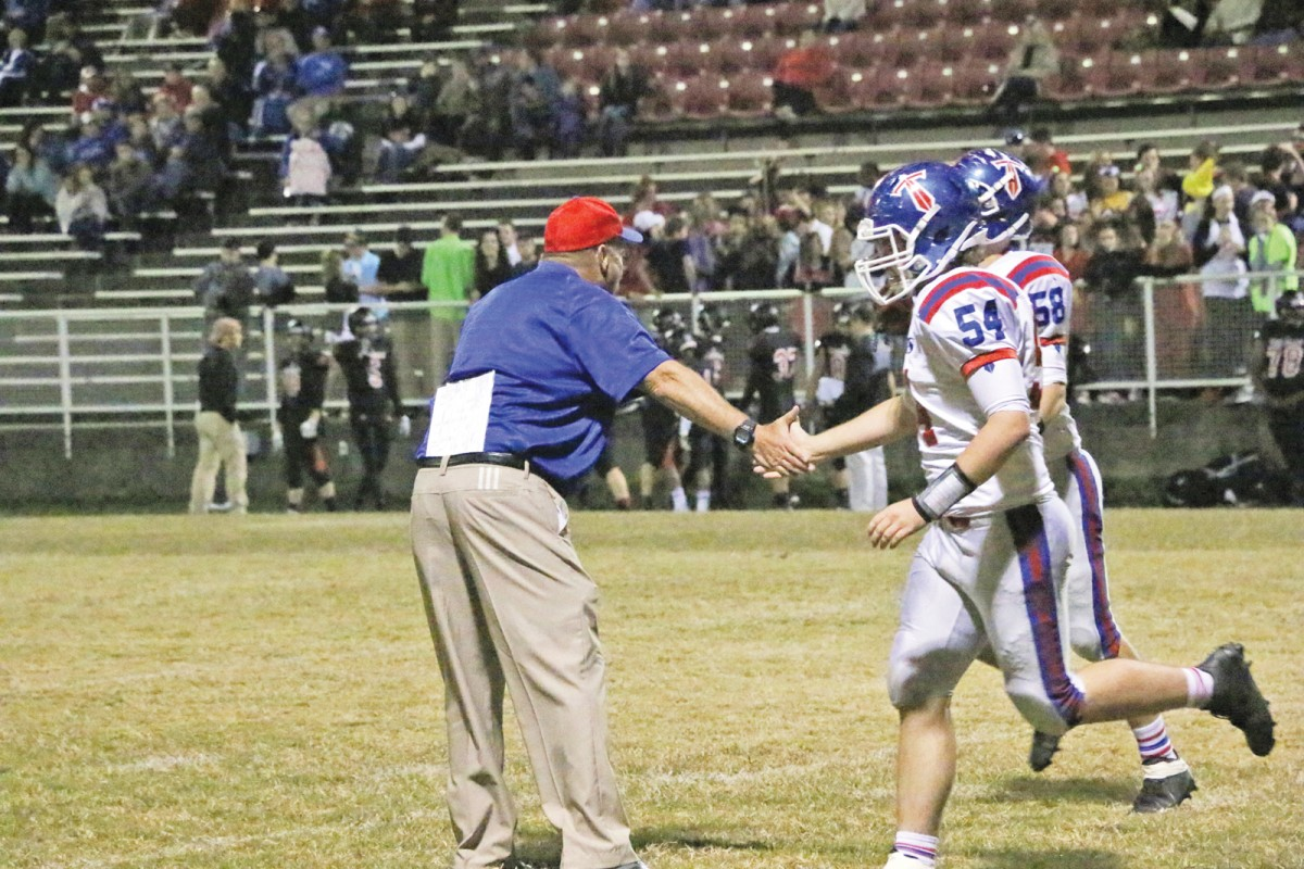 Mercer County Football Coach David Buchanan, left, celebrated with players following a touchdown in the second quarter. The Titans defeated George Rogers Clark 43-0.