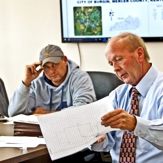 Larry Catlett (right), attorney for the Mercer County Sanitation District, goes over a property damage claim to the board of directors, including Bruce Wade (left).
