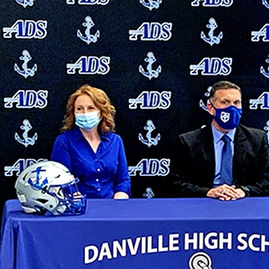 Photo Submitted It was announced at a press conference that Mark Peach, right, will take over as football coach for the Danville Admirals, his wife Julia joined him.
