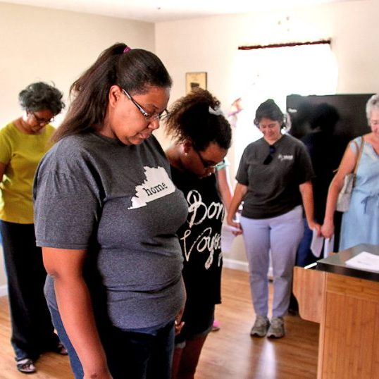 Latricia Smith and Asia Mattingly stand in the middle of a prayer circle with members of Mercer County Habitat For Humanity in this 2017 file photo. The nonprofit is holding a benefit in order to continue providing local low cost housing.